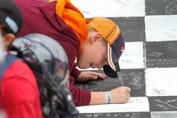 A child draws on the start-finish line