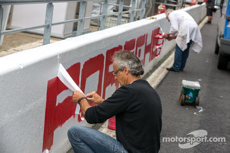 Operai preparano la scritta Porsche sul muro dei box
