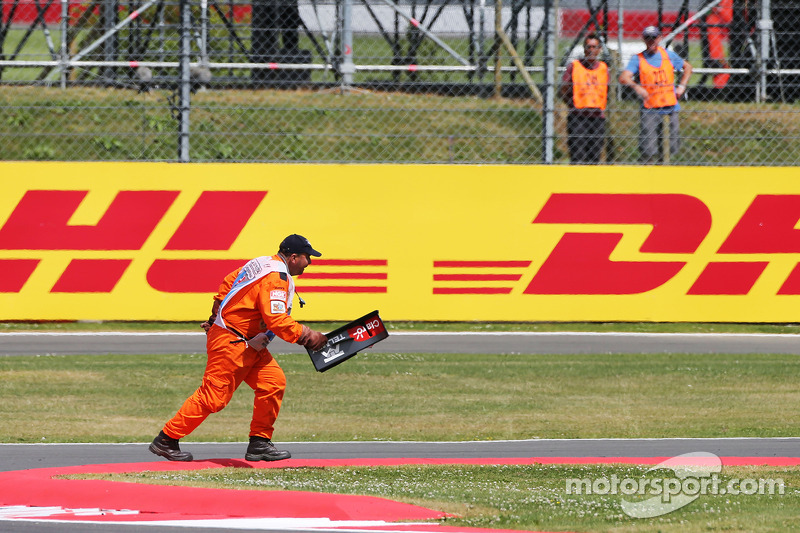 A marshal removes debris from the circuit