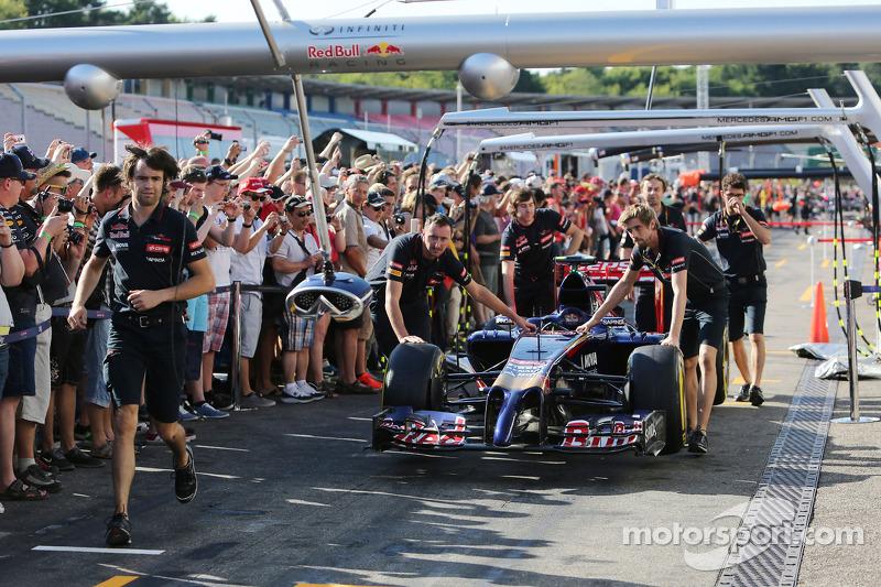 Scuderia Toro Rosso STR9 pit alanında itilirken taraftarlar pitte
