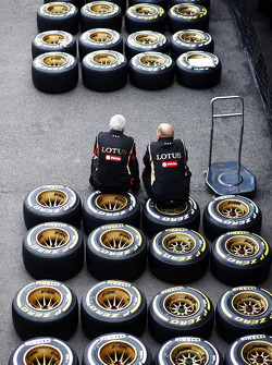 Lotus F1 Team mechanics sit on Pirelli tyres