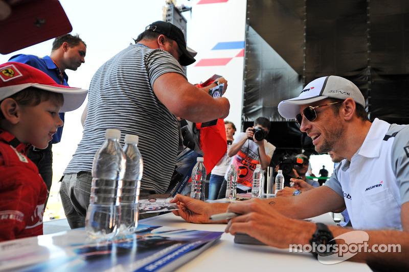 Jenson Button, McLaren firma autografi per i fan presso la Fanzone