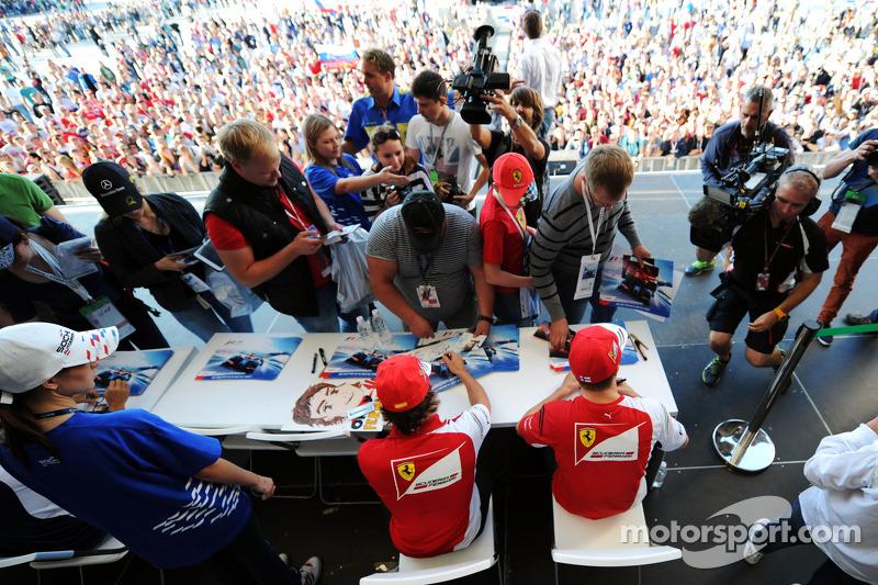 (L to R): Fernando Alonso, Ferrari and team mate Kimi Raikkonen, Ferrari sign autographs for the fan