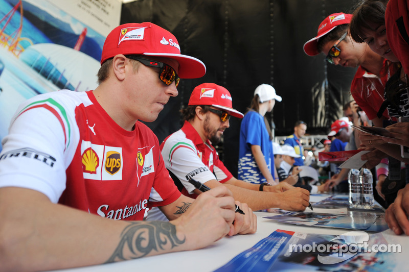(L to R): Kimi Raikkonen, Ferrari and team mate Fernando Alonso, Ferrari sign autographs for the fans at the Fanzone