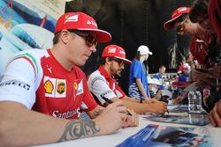 (Da sinistra a destra): Kimi Raikkonen, Ferrari e il compagno di squadra Fernando Alonso, Ferrari firmano autografi per i fan