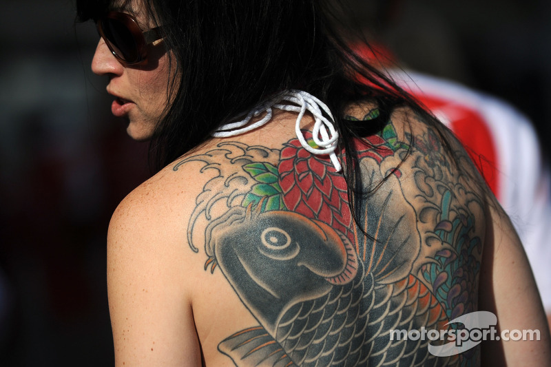 A woman with a tattoo of a fish on her back
