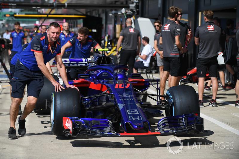 Meccanici della Scuderia Toro Rosso con una Scuderia Toro Rosso STR13