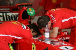 Ferrari team members refill the water tank