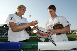 Jennie Finch of the Chicago Bandits softball team and NASCAR driver Carl Edwards sign a pennant for a fan during the Racin' the Bases Celebrity Softball game benefitting the Victory Junction Gang Camp