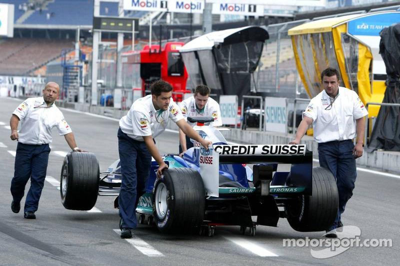 Los miembros del equipo Sauber empujar el coche en el garaje