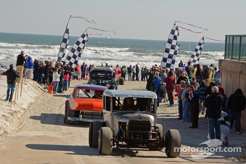 Klassische Fahrzeuge absolvieren eine Fahrt am Strand vor den Augen der Zuschauer