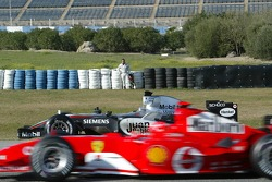 Michael Schumacher passes Juan Pablo Montoya stopped on the track