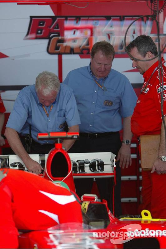 Des délégués techniques de la FIA inspectent la Ferrari