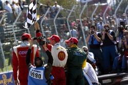 Race winner Sébastien Bourdais celebrates with Justin Wilson and Alex Tagliani