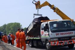 La voiture de Mika Hakkinen soulevée par un camion après sa dérivation de la piste