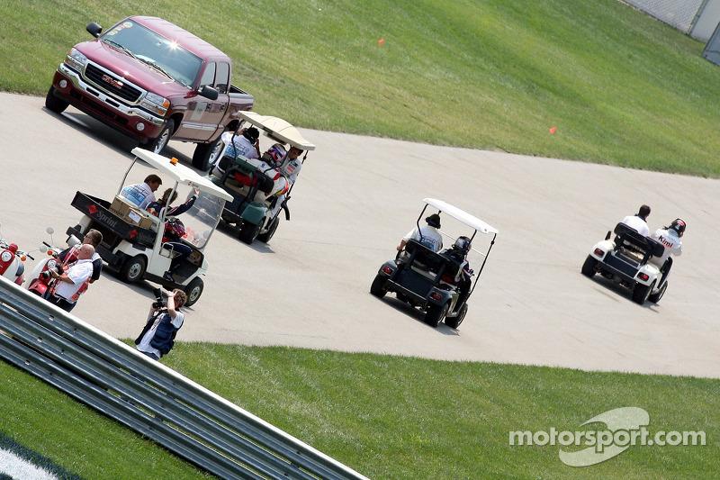Des pilotes retounent aux stands dans des voiturettes de golf