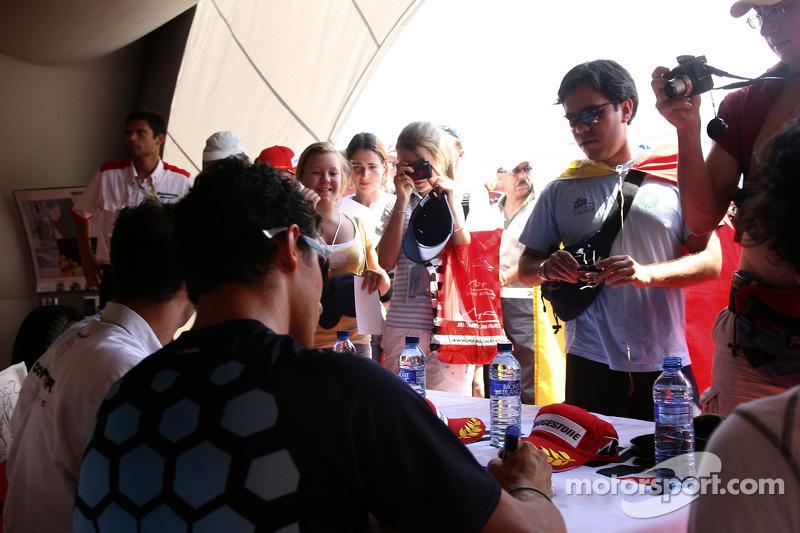 Andreas Zuber, Jose Maria Lopez et Lucas Di Grassi et Alexandre Negrao signent des autographes dans la tente de Bridgestone