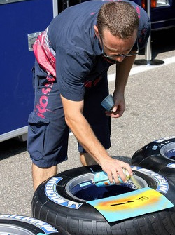 Scuderia Toro Rosso team member sprays paint onto tyre walls of their Michelin tyres