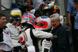 Race winner Jenson Button celebrates with Rubens Barrichello