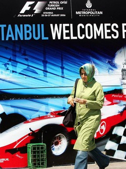 A woman with a scarf walks in front of an advertising banner in downtown Istanbul