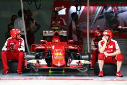 Ferrari-Mechaniker sitzen neben dem Ferrari SF15-T von Kimi Räikkönen, Ferrari