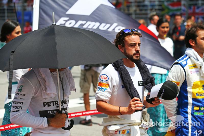 Lewis Hamilton, Mercedes AMG F1 y Fernando Alonso, McLaren en la parrilla observan el himno nacional