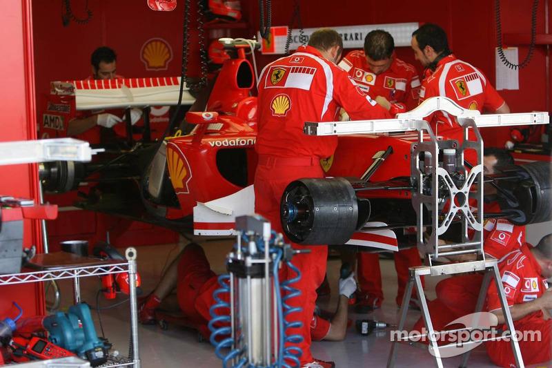 Des mécaniciens travaillent sur la voiture de Michael Schumacher