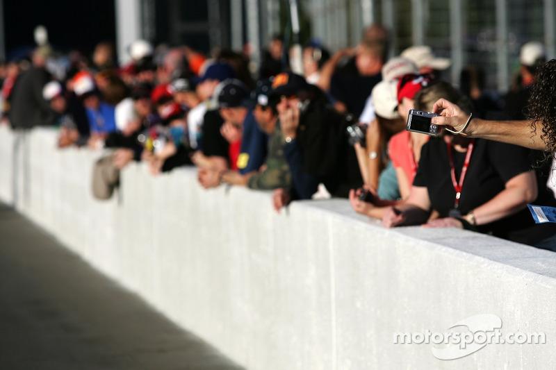 Des fans prennent des photos de l'action sur la grille