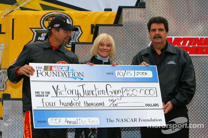 Le Président de la NASCAR Mike Helton présente un chèque à Pattie et Kyle Petty pour le Victory JunctionGang