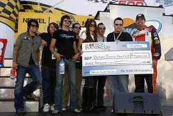 The music group Smash Mouth presents a check to Kyle Petty and the Victory Junction Gang Camp
