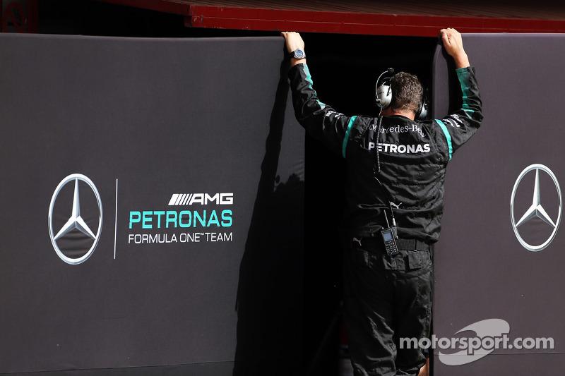 Mercedes AMG F1 mekanikeri garaj önünde perdeleri düzeltiyor