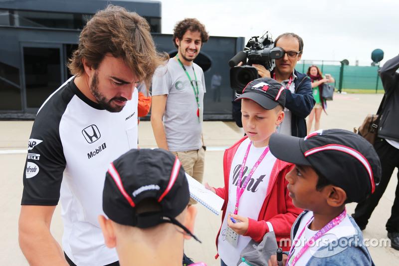 Fernando Alonso, McLaren, schreibt Autogramme für Kinder von F1 in der Schule