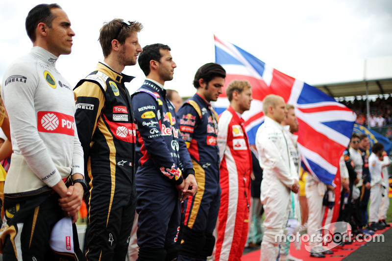 Pastor Maldonado, Lotus F1 Team, dan Romain Grosjean, Lotus F1 Team as the grid observes the national anthem