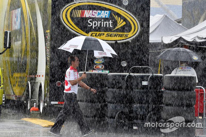Seorang anggota tim Chip Ganassi Racing crew berjalan di tengah hujan