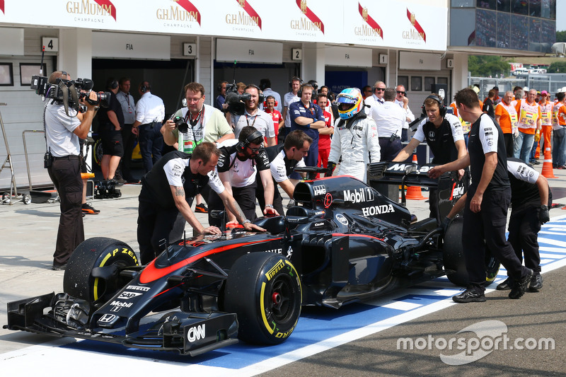 The McLaren MP4-30 of Fernando Alonso, McLaren is pushed into the pits during qualifying
