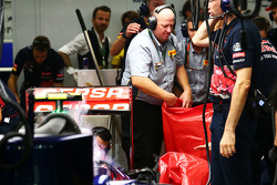 Инженеры Pirelli снимают поврежденное заднее колесо с машины Карлоса Сайнса мл., Scuderia Toro Rosso