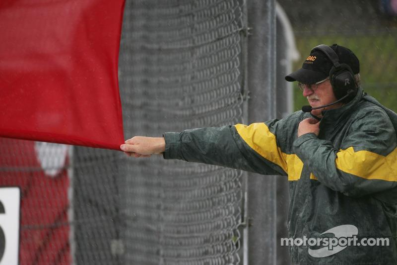 Un oficial de pista ondea la bandera a cuadros