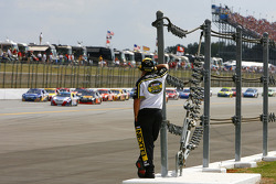 A NASCAR official watches as the pack thunders down the long backstretch at Talladega Superspeedway