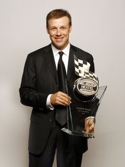 Matt Kenseth holds the trophy given to the fourth place driver in the NASCAR NEXTEL Cup Series standings