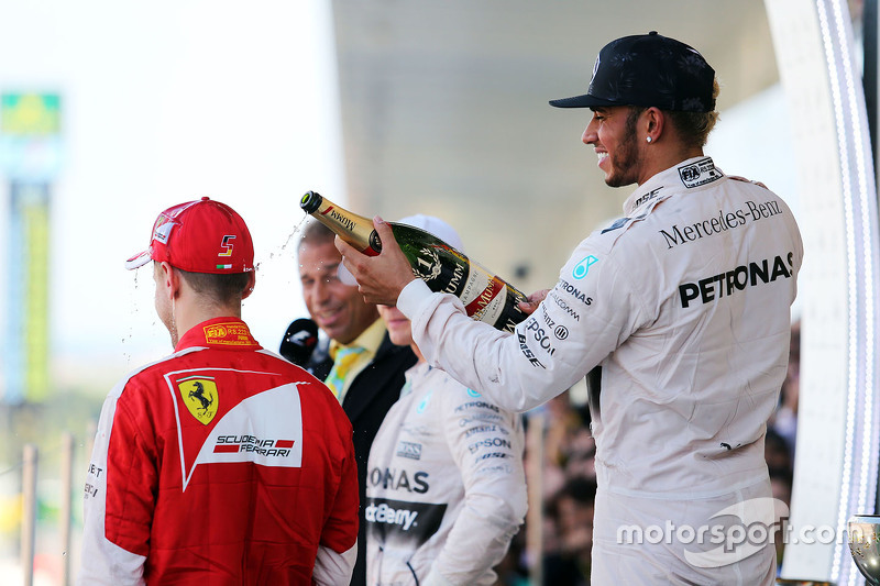 Race winner Lewis Hamilton, Mercedes AMG F1 celebrates on the podium with third placed Sebastian Vet