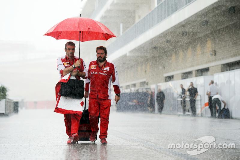 (L to R): Maurizio Arrivabene, Ferrari Team Principal with Gino Rosato, Ferrari in a wet and rainy paddock