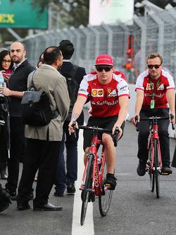 Кими Райкконен, Ferrari едет по трассе на велосипеде