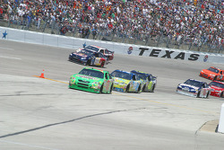 Kyle Busch leads a line of cars to the pit lane
