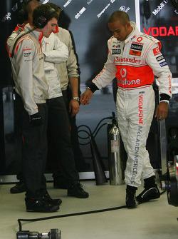 Lewis Hamilton, McLaren Mercedes, balancing on the air line for the wheel nut guns