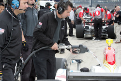 Crew members fill the cars by hand during practice