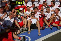 Timo Glock celebrates with Jarno Trulli and Toyota F1 team