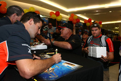 Jamie Whincup signs an autograph for a fan