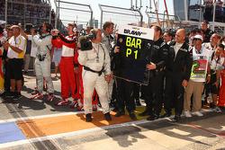 Brawn GP team members wait for race winner Rubens Barrichello