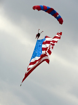 Parachuters bring the American Flag down to the start finish line