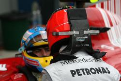 Michael Schumacher, Mercedes GP talks to Fernando Alonso, Scuderia Ferrari
